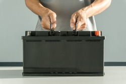 Auto mechanic holding car battery, Technician replacing car battery, Cconcept car inspection, maintenance, checking