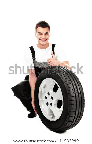 Auto mechanic holding car wheel isolated smiling