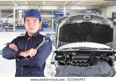 Auto mechanic holding wrench at maintenance repair service station
