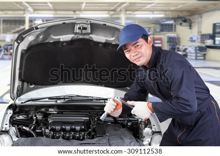 Auto mechanic holding wrench for working in garage repair service