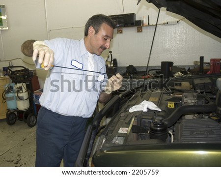 auto mechanic is checking fluid levels on an automobile that is being repaired