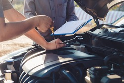 Auto mechanic is checking oil and repair a car in outdoor, Car repair service concept.