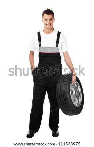 Auto mechanic isolated holding car wheel smiling