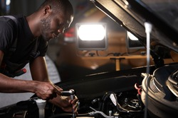 auto mechanic male use wrench and other tools for fixing a car engine, working alone