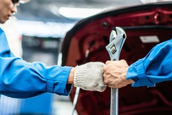 auto mechanic man holding wrench bumping fists with team colleague worker in auto repair shop. concept of teamwork working for car maintenance service industrial. automotive business manufacturing