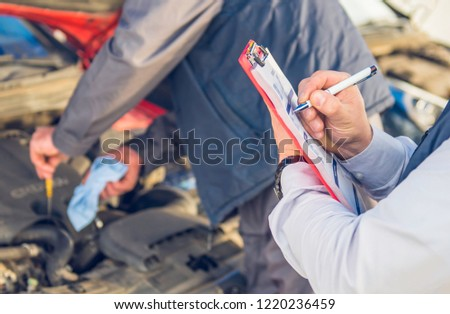 Auto mechanic perform vehicle checkup while service advisor take notes - Professional Auto Service Technician - concept of inspecting and taking care of the car