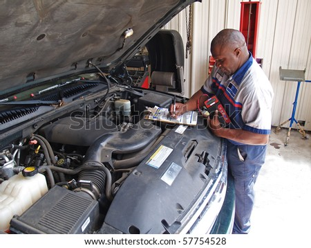 Auto mechanic performing a routine service inspection in a service garage.