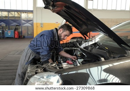 auto mechanic repairing a car engine - stock photo
