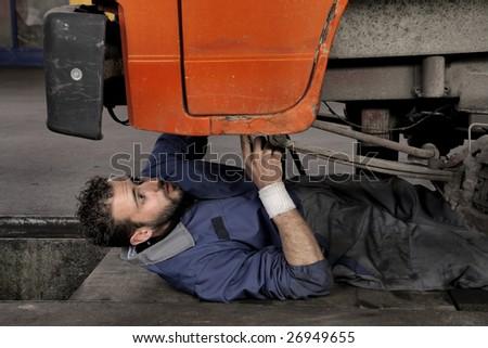 auto mechanic repairing a vehicle - stock photo