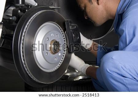 auto mechanic repairing brake caliper
