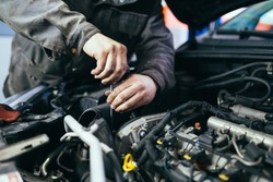 Auto mechanic repairing car. Selective focus.
