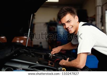 Auto mechanic repairing car smiling.