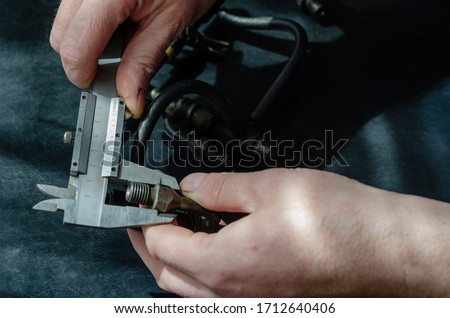 Auto mechanic repairs fuel diesel injectors. The hands of an adult male are measured with a caliper. A set of injectors for a turbo diesel engine on a table in a workshop. Car service. Selective focus