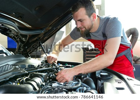 Auto mechanic repairs vehicle in a workshop  #786641146