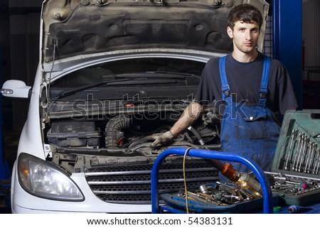 Auto mechanic standing near car at repair shop
