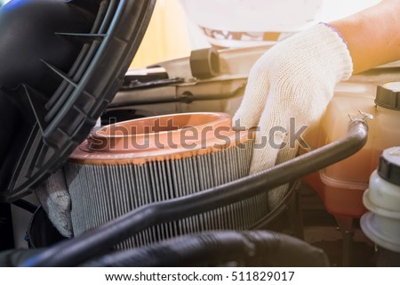 auto mechanic wearing protective work gloves holding a dirty, air filter over a car engine for cleaning #511829017