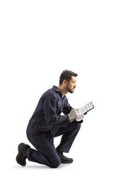 Auto mechanic worker in a uniform kneeling and writing a document isolated on white background