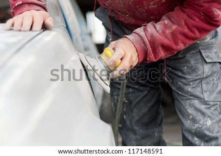 auto mechanic worker polishing the basic layer of car body