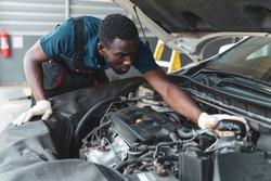 Auto mechanic working in garage, car repair services