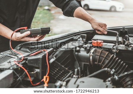 Auto mechanic working in garage Technician Hands of car mechanic working in auto repair Service and Maintenance car battery check.