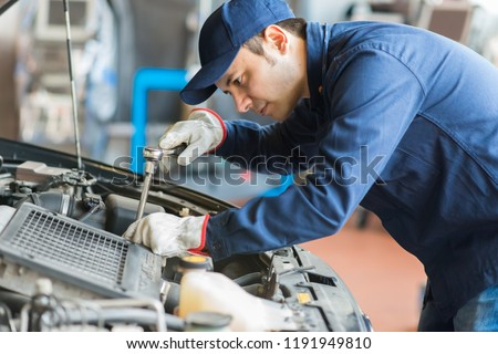 Auto mechanic working on a car in his garage #1191949810