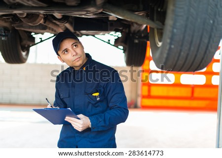 Auto mechanic working on a car in his garage #283614773