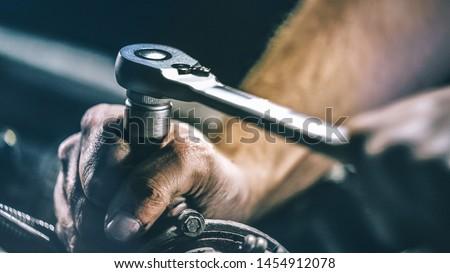 Auto mechanic working on car engine in mechanics garage. Repair service. authentic close-up shot #1454912078