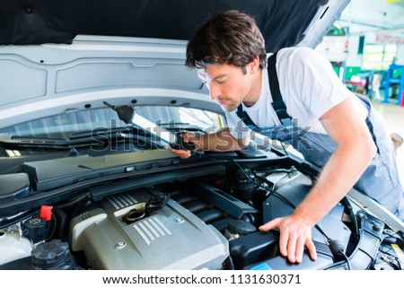Auto mechanic working on car in service workshop #1131630371