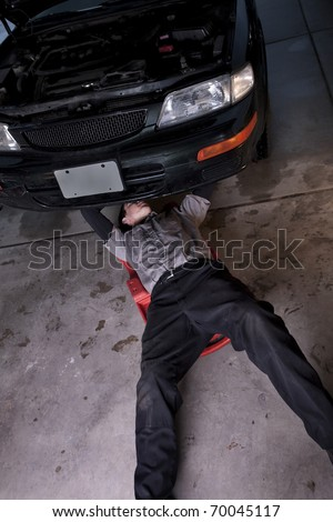Auto mechanic working under a car repairing an engine