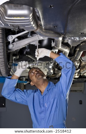 auto mechanic working under car on a lift