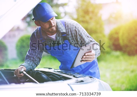 Shutterstock Auto mechanic working with digital tablet and wrench in engine. Car repair service with digital inspection