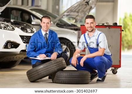 Auto mechanics posing at camera with tire.