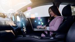 Auto pilot self driving car businesswoman working using computer laptop, HUD Head Up Display and digital instruments panel autonomous user interface navigation utility screen smart technology hologram