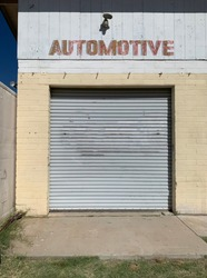 Auto repair garage with door and Automotive sign painted on the building