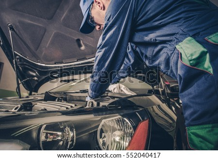 Auto Service Business Concept. Pro Car Mechanic Taking Care of Vehicle. Checking Under the Car Hood.