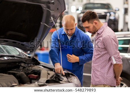 Shutterstock auto service, repair, maintenance and people concept - mechanic with clipboard and man or owner looking at broken car engine at shop