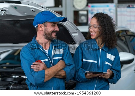 Auto services and Small business concepts. Auto mechanic hands using wrench to repair a car engine. Two happy auto mechanics in uniforms working in auto service.