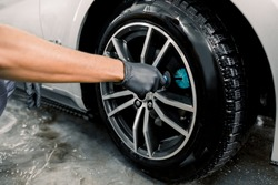 Auto wash service. Cropped close up image of male hands in black protective gloves, cleaning alloy wheels rims of luxury car with a special brush for cast wheels in a vehicle detailing workshop