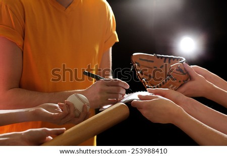 Autographs by baseball star on black and lights background