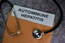 Autoimmune Hepatitis text with document brown envelope and stethoscope isolated on office desk.