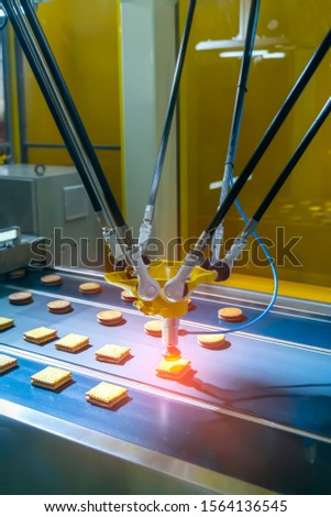 automate robot with vacuum suckers with conveyor in Production of biscuits in a manufacture factory for the food industry
