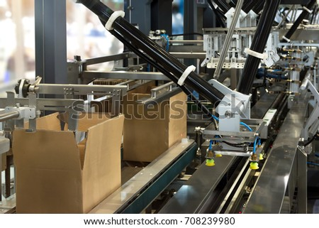 Automated conveyor systems , modular conveyors and industrial automation for package transfer manufacturing production machine , robot arm in smart factory and industry 4.0 concept.