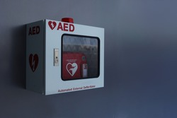 Automated External Defibrillator (AED) in white box on the wall.Heart defibrillator on gray background.
