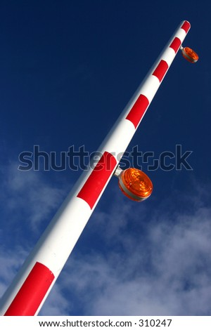 Automated parking bar raised against a blue sky