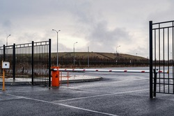 Automatic barrier of orange color with a white stripe and red warning stripes, for the entry of cars. Entrance to the car factory parking lot.