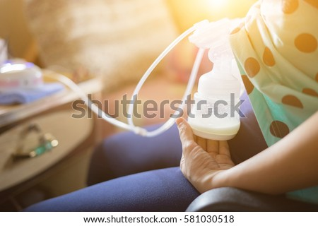 Automatic breast pump, mothers breasts milk is the most healthy food for newborn baby. Happy mother with babys at bed room ,home,vintage color