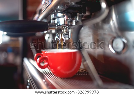 Automatic espresso machine pouring coffee in cups at restaurant or pub. Barista concept with machinery, tamper, coffee and tools
