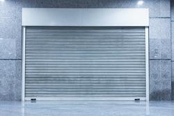 Automatic Factory Shutter Roller Door Indoor, Steel Rolling Gate Door for Security System of Warehouse Storage. Architecture Metal Access Doorway With Granite Wall Background of Workshop Garage.