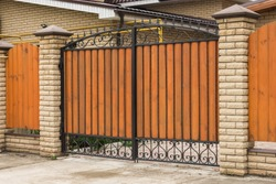 Automatic gates made of wood with forged elements in the cottage