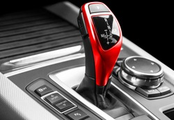 Automatic gear stick of a modern car. Modern car interior details. Close up view. Car detailing. Automatic transmission lever shift. Black leather interior with red stitching.